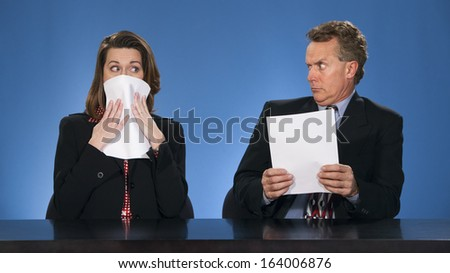 Male newscaster looking at female co-worker as if she has said something terrible. - stock photo