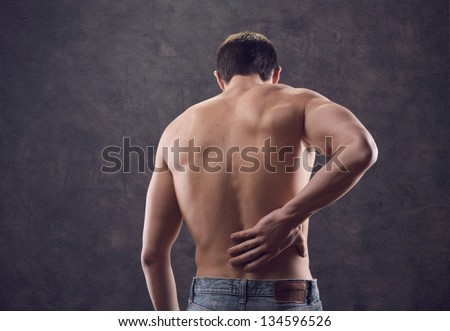male nude from behind holding hand to spot of back pain - stock photo
