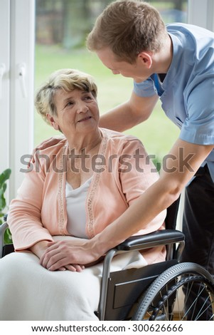 Male nurse and older woman on wheelchair