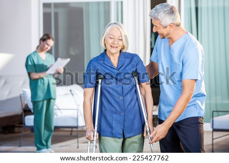 Male nurse helping senior woman to use crutches with caretaker in background at nursing home - stock photo