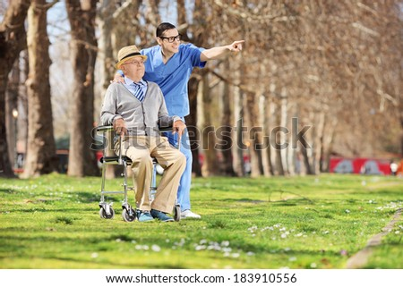 Male nurse showing something to a senior in wheelchair outdoors - stock photo