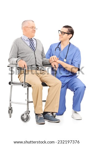 Male nurse talking to a senior patient seated in a wheelchair isolated on white background - stock photo
