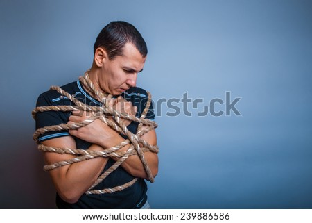 male of European appearance brunet lowered his head tied with a rope on a gray background - stock photo