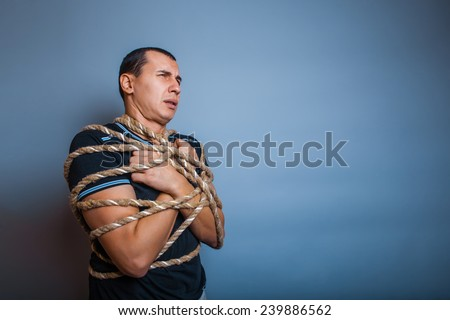 male of European appearance brunet tied with a rope around the body on a gray background - stock photo