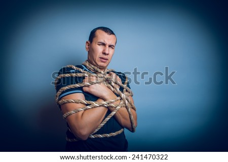 male of European appearance brunet tied with rope on a gray background cross process - stock photo