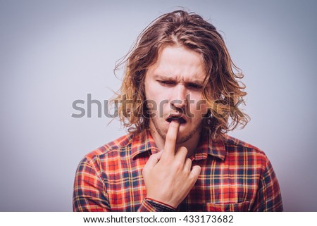 male of European appearance causes vomiting putting his fingers in his mouth on a gray background, nausea - stock photo