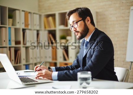 Male office worker browsing in laptop for necessary information - stock photo