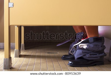 male office worker in a bathroom stall - stock photo