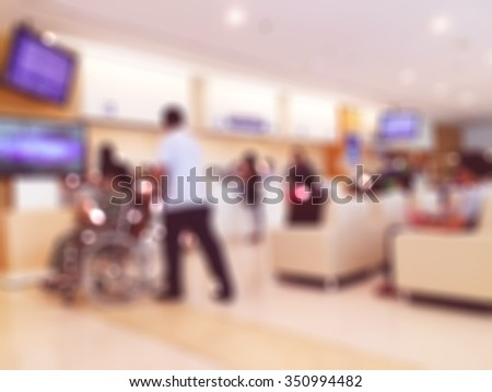 Male officer in hospital sliding wheels chair in out patient department of the hospital - stock photo