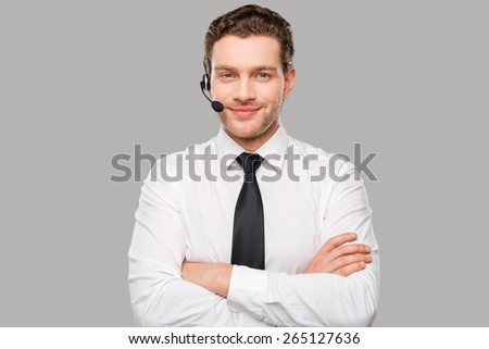 Male operator. Handsome young man in formalwear and headset looking at camera and smiling while standing against grey background - stock photo