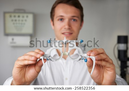 Male Optician Giving Patient Sight Test - stock photo
