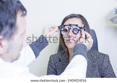 male optometrist is calibrating the eye test glasses phoropter to exam the eyesight to a young patient woman - focus on the center of the glasses