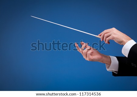 Male orchestra conductor hands, one with baton. Blue background. - stock photo