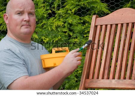 male outside garden painting deck chair - stock photo