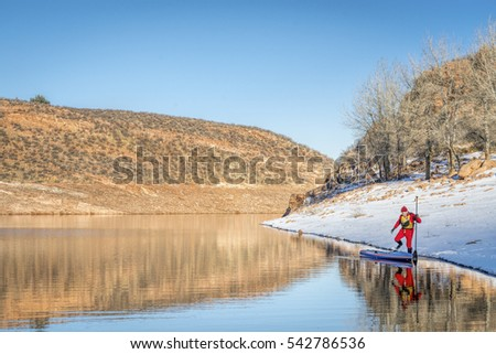 male paddler in drysuit is launching a stand up paddleboard on mountain lake in Colorado, winter scenery