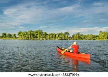 male paddler paddling a red canoe on a local lake in Fort Collins, Colorado