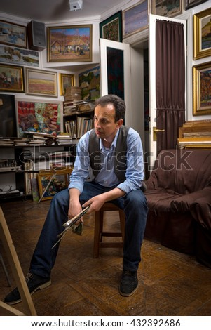 Male painter sitting thinking in a studio with a paint brush and rag in his hand with a dejected expression as though not happy with the result - stock photo