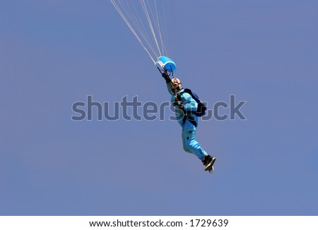 Male parachutist wearing a blue boiler suit, flying against a blue sky.