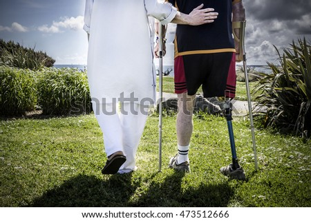 Male patient amputee wearing a prosthetic leg standing with a physiotherapist in a park, near the rehabilitation center