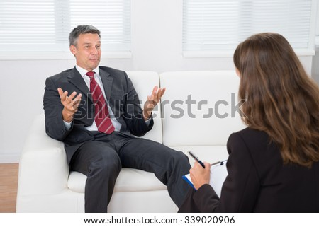 Male Patient On Couch Talking With Professional Psychiatrist - stock photo