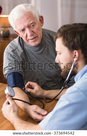 Male patient with hypertension in cardiologist's office - stock photo