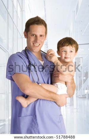 Male pediatrician holding a baby boy - stock photo