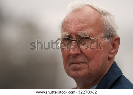 Male pensioner wearing spectacles with serious expression - stock photo