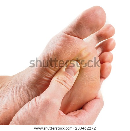 Male person receiving podiatry with pressure point technique under foot isolated towards white - stock photo