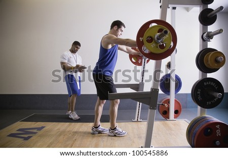 Male personal trainer with male client lifting weights - stock photo