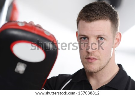 Male personal trainer with work-out pads - stock photo