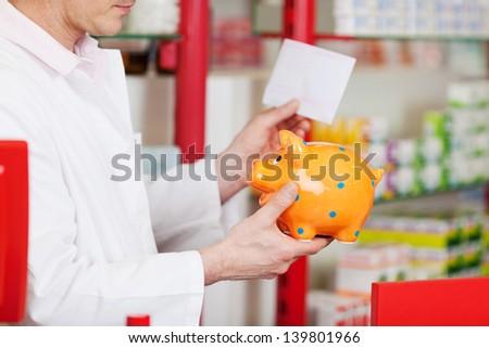 male phamarcist holding orange piggy bank - stock photo