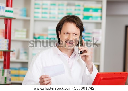 male pharmacist on call in a pharmacy with prescription - stock photo