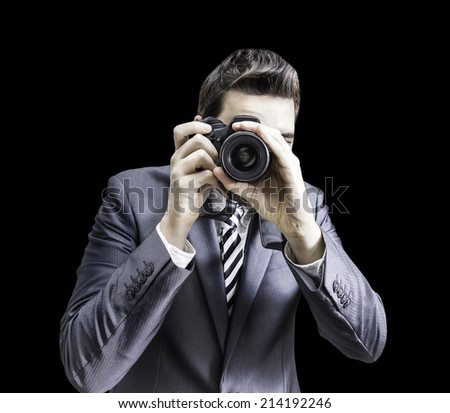 Male photographer focusing and composing an image with his professional digital SLR camera pointing the lens directly at the viewer on black background - stock photo