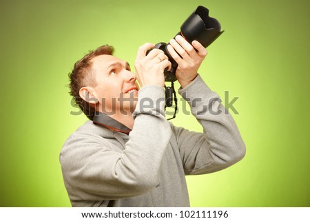 Male photographer taking photos with DSLR digital camera - stock photo