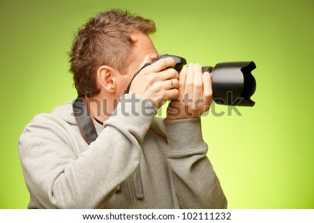 Male photographer taking photos with DSLR digital camera, side view - stock photo