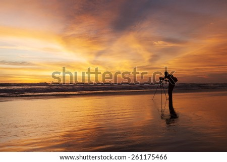 Male photographer taking picture with dslr camera on the beach at sunset time - stock photo