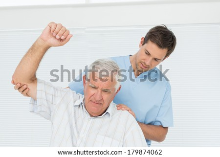 Male physiotherapist assisting senior man to raise hand in the medical office - stock photo