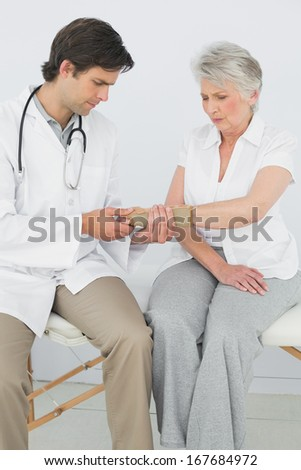 Male physiotherapist examining a senior woman's wrist in the medical office - stock photo