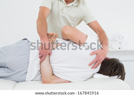 Male physiotherapist examining man's back in the medical office