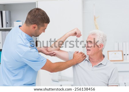 Male physiotherapist giving massage to senior man in clinic