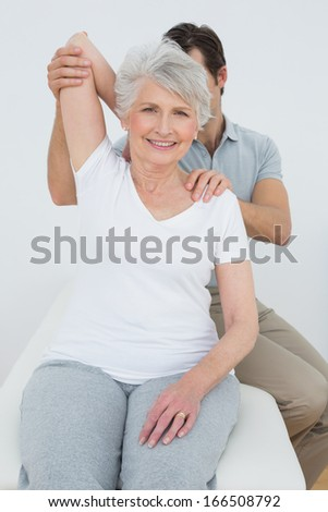 Male physiotherapist stretching a smiling senior woman's arm in the medical office - stock photo