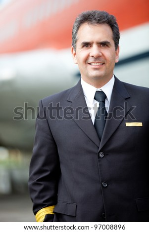 Male pilot in his uniform outdoors at the airport - stock photo