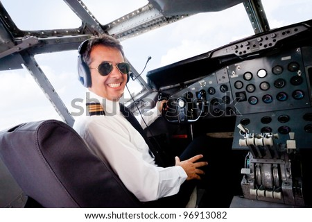 Male pilot sitting in an airplane cabin flying and smiling - stock photo