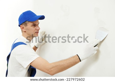 male plasterer at indoor wall renovation decoration with spatula and plaster - stock photo