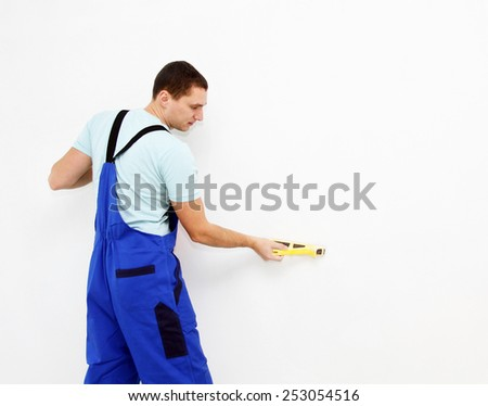 Male plasterer in uniform polishing the wall - stock photo
