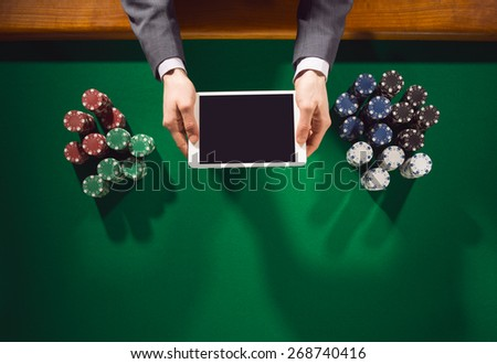 Male player holding a digital tablet and playing with stacks of chips all around on a green table, top view - stock photo