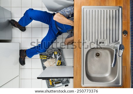 Male Plumber Examining Sink In Kitchen Holding Clipboard - stock photo