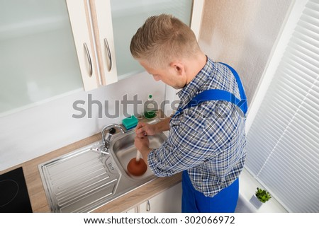 Male Plumber Using Plunger In Stainless Steel Sink In Kitchen - stock photo
