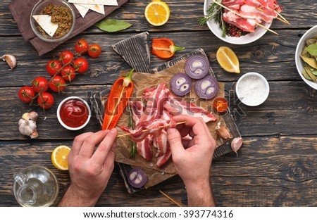 male preparing skewers of grilled bacon. Top view - stock photo