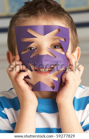 Male Primary School Pupil Cutting Out Paper Shapes In Craft Lesson - stock photo